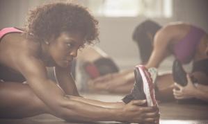 Black women stretching in gym